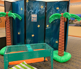 discovery bin with water and starfish along with inflated palm trees and a folding wall with blue translucent paper and stars