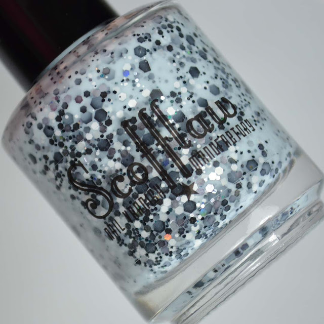 light blue nail polish with glitter in a bottle