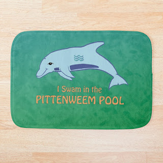 A bathmat with I swam in the Pittenweem pool and a dolphin on it