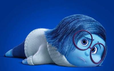 El personaje Tristeza de la película de Pixar Del Revés, tumbada en el suelo con aire apático