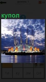 На воде вдалеке стоит необычный купол с освещением круглой формы зданием с высокими мачтами