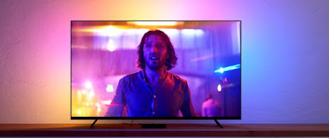 Large TV with a person and bright colours showing on the screen as well as neon vivid pinks and yellows emanating from behind the TV