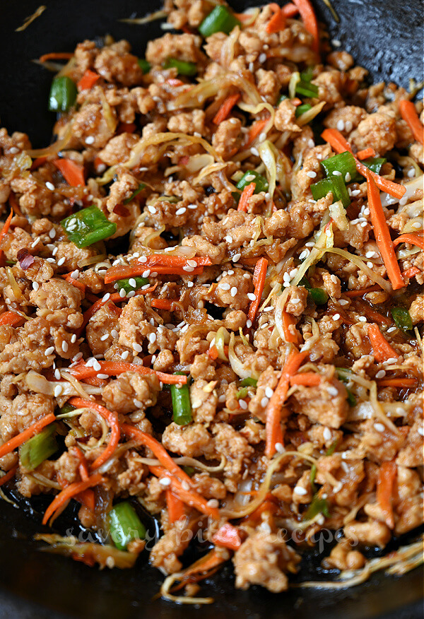 a close up of pan with thai chicken topped with sesame seeds