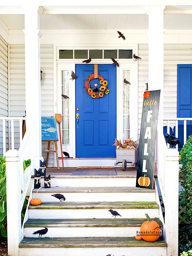 Front porch with blue door and black crows and hello Fall sign