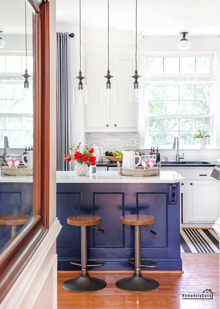 Navy kitchen island, red roses and white cabinets