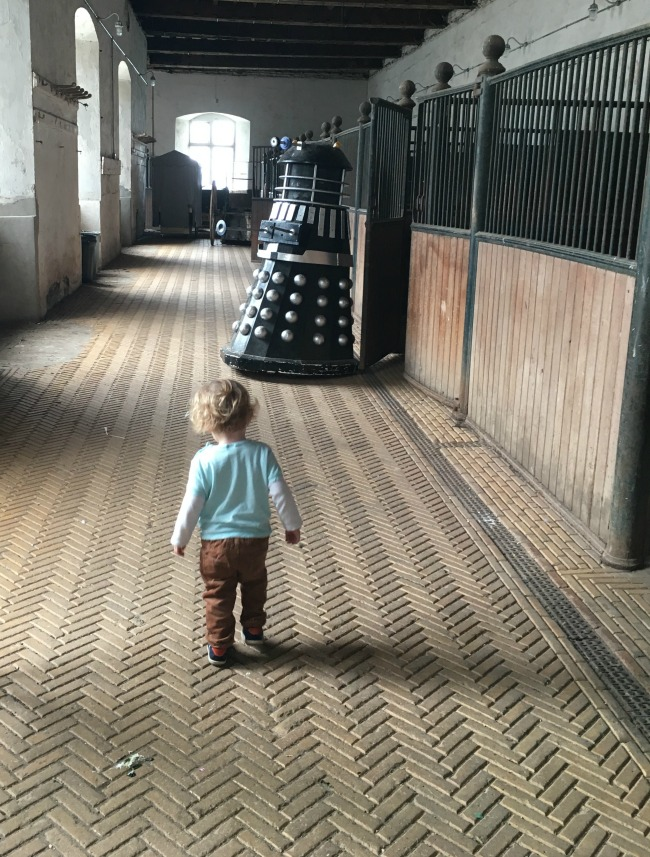 Tredegar-House-&-gardens-inside-stables-with-toddler-walking-towards-a-dalek