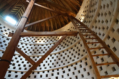 Interior of a dovecote: the walls are white, with a checkerboard pattern of square niches for the pigeone; a central wooden post extens to the roof, with a ladder which is curved to match the curve of the dovecote.