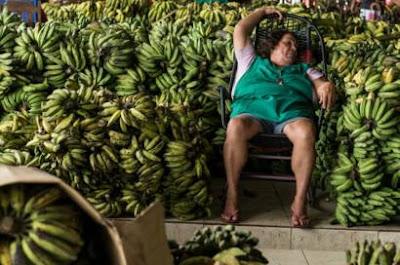 Mujer dormida rodeada de bananas.