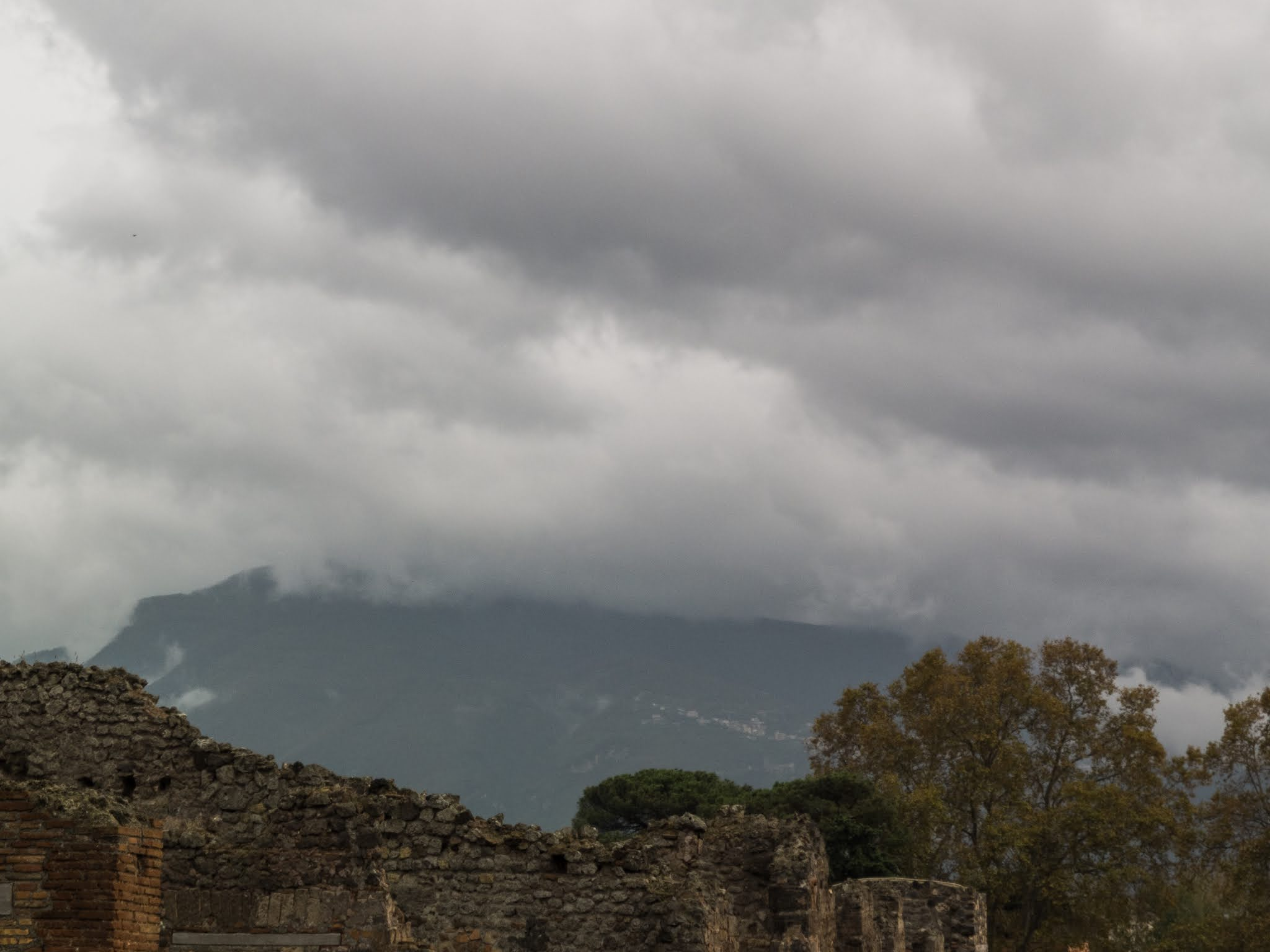 View of ancient Pompeii and Mount Vesuvius on a cloudy day.