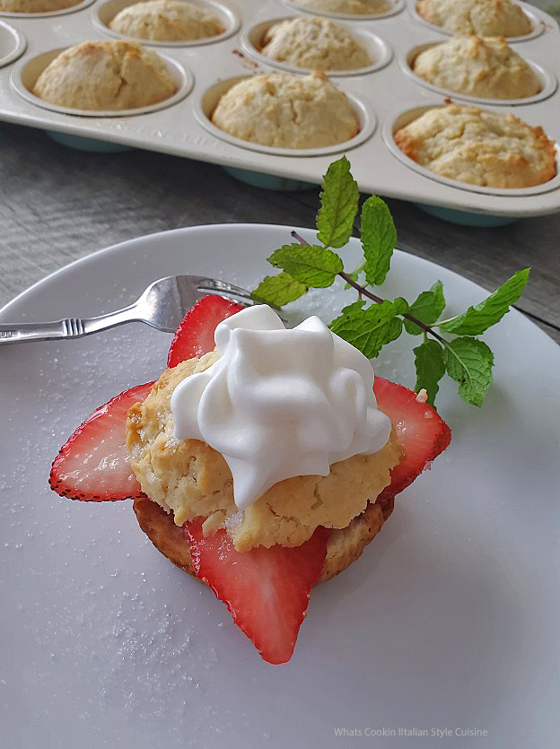 this is a biscuits with sliced strawberries arranged in points topped with another biscuit then whipped cream. This is on a white plate with a sprig of mint in the back ground and you can see the other biscuits in a cupcake tin in the background all sitting on wooden board.