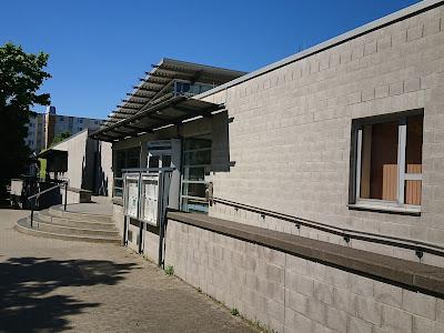 Blck auf den Eingangsbereich. Vorne, flach, quadratisch grau, das Hallenbad, hinten mit hohem Dach das Sportbad.
