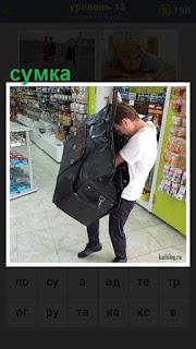 в магазине мужчина ищет что то в своей большой сумке