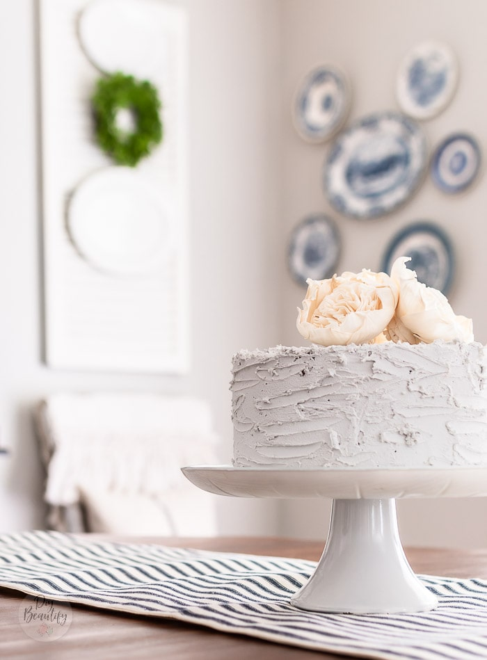 fake cake on stand, blue plates on wall and white shutters as decor