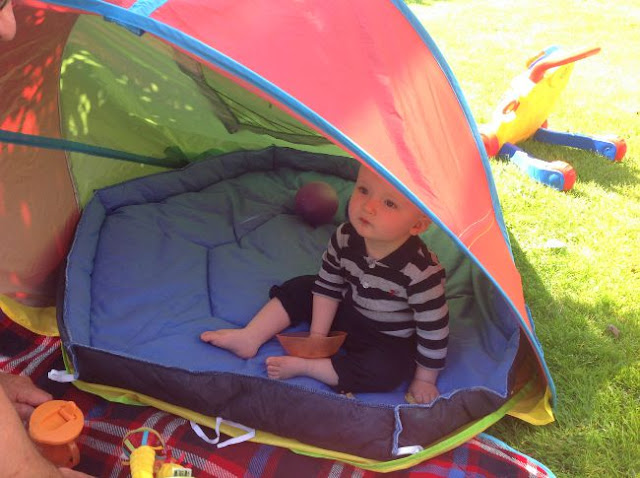 baby in sun tent in garden with orange bowl of food