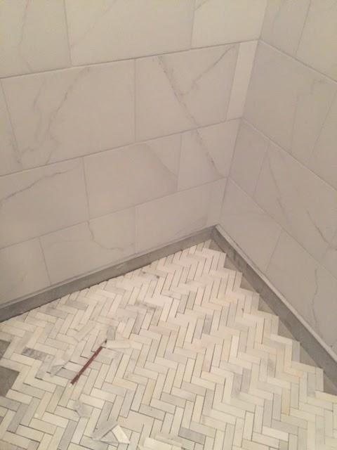 Herringbone marble mosaic tile shower floor under construction - Hello Lovely