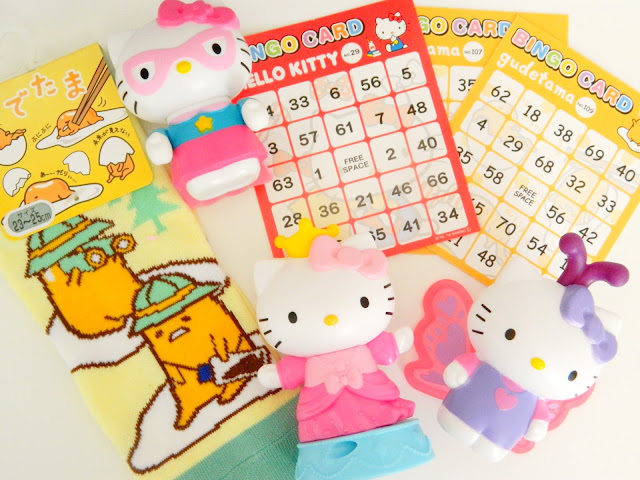 a photo showing cute egg character socks, cute character bingo cards and hello kitty figurines; a superhero, a butterfly and a princess