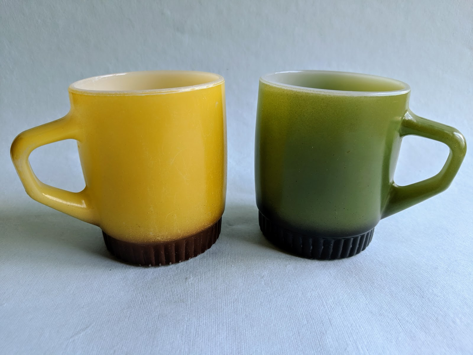 Photo of two retro color glass mugs. one yellow, one green