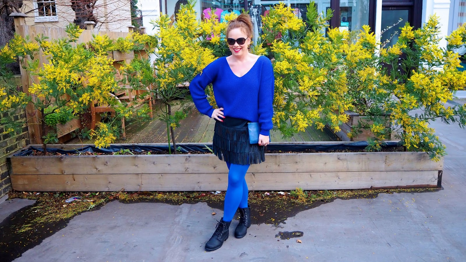 royal blue sweater and tights, black leather fringe skirt, blue leather clutch, black biker boots