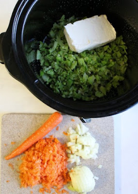 slow cooker with broccoli and cream cheese, carrots and onions on cutting board