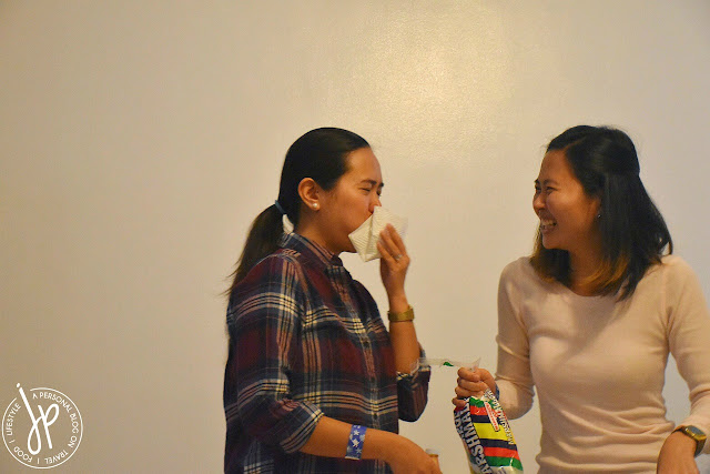 woman covering mouth, woman holding bag of marshmallows while laughing