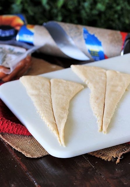 Preparing Crescent Roll Triangles to Make Pigs In a Blanket With the Works Image