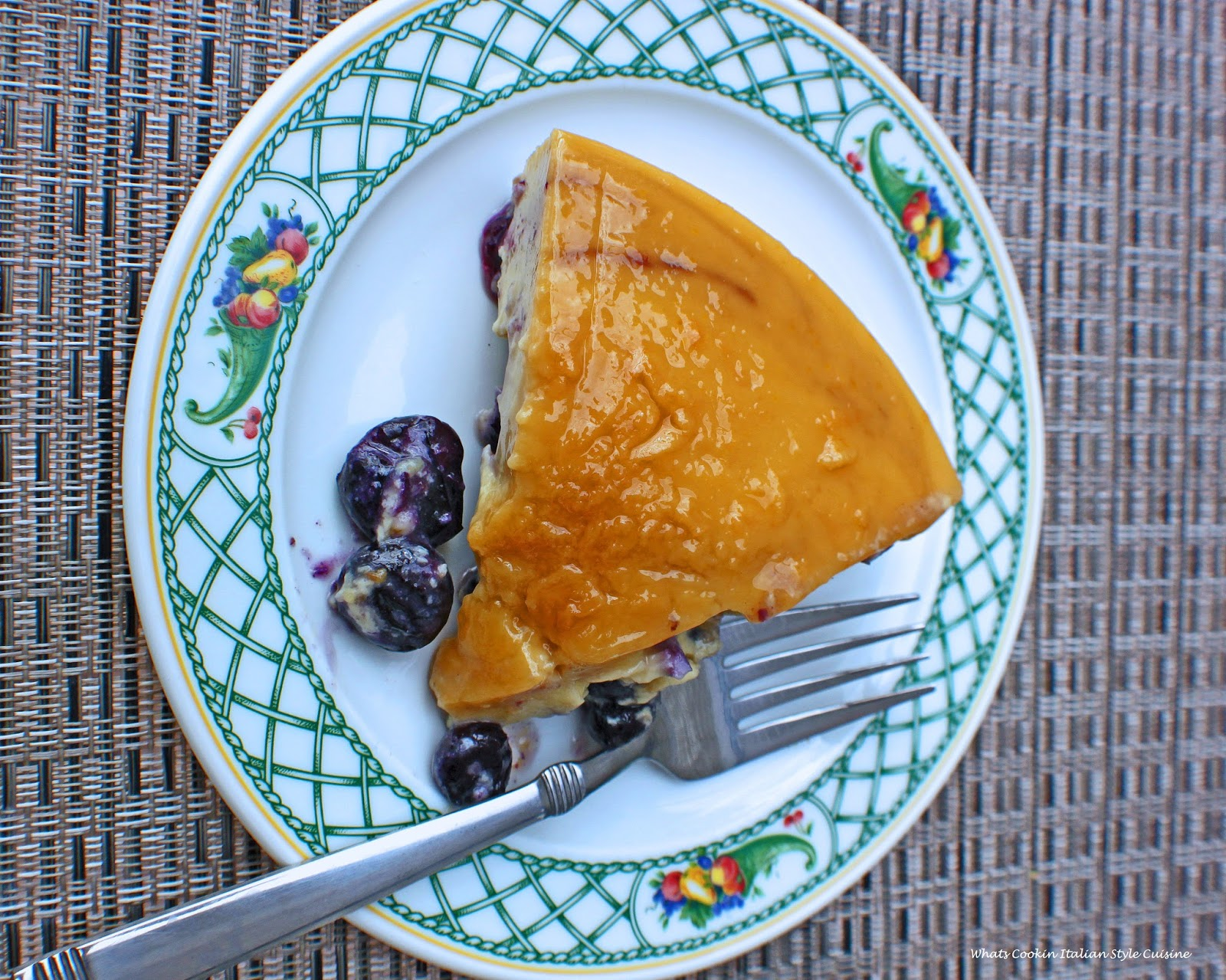 Sliced Blueberry Flan on a fruit trim Lenox china plate showing the flan that will be served