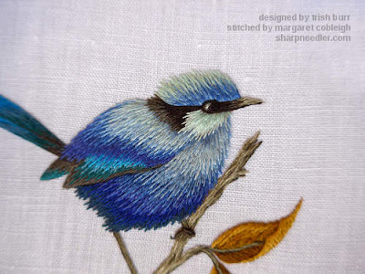 Close-up of thread painted blue bird showing added shadows and details