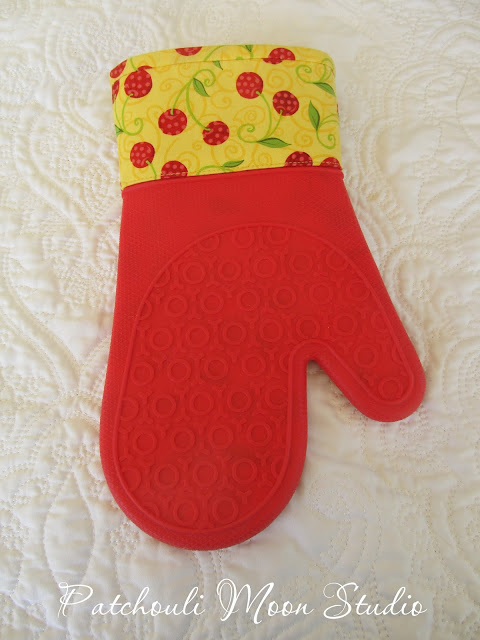Oven mitt in yellow and red cherry fabric with red silicone.