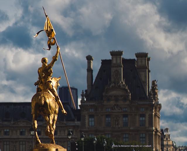 Joana D'Arc em uma estátua dourada, empunha estandarte, iluminada por luz indireta do sol, com prédios ao fundo