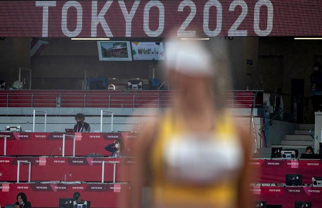 competidora desfocada em primeiro plano e tribuna de imprensa ao fundo com sinal tóquio 2020