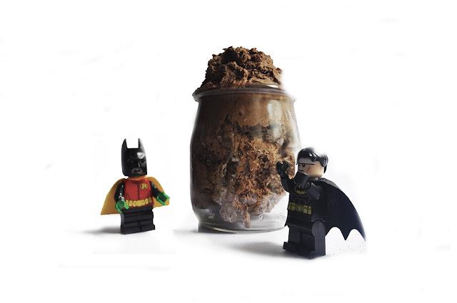 un robin de lego con la mascaras de batman es descubierto por el `propio batman, detrás una mousse de chocolate