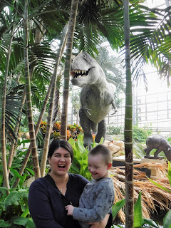 a woman roars while a boy laughs, and a tyrannosaur statue and large tropical plants are visible in the back