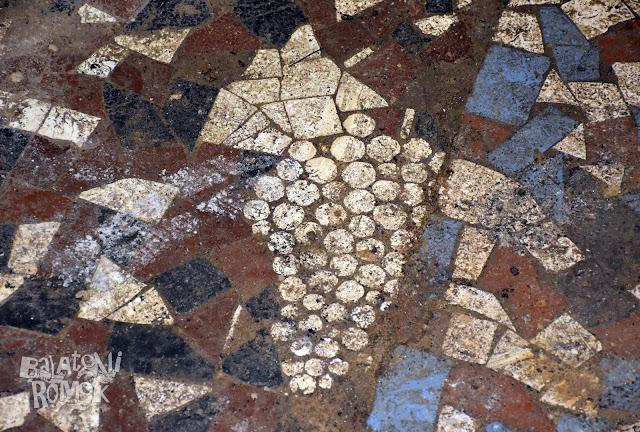 Színes metlakiból kirakott szőlőfürt a padlón