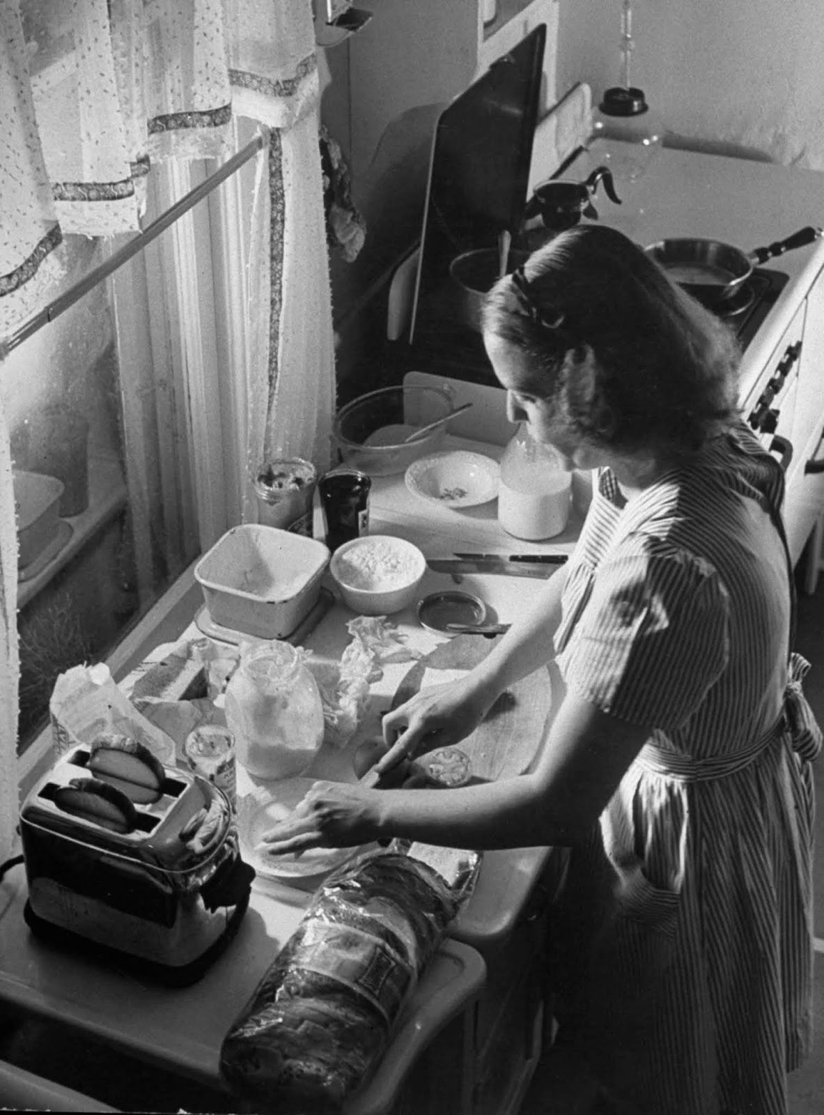 Jane using pop-up toaster, as she makes sandwiches for her three children.
