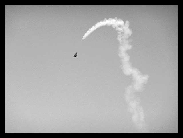 Humo de un avión haciendo piruetas en el aire.