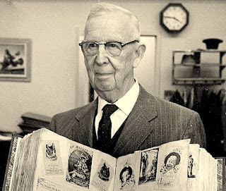 Earl J. Arnold holds his mother's trade card scrapbook in his Waltham Chamber of Commerce Office in 1960 or so.