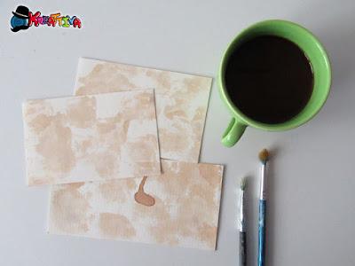 invecchiare con il caffè la carta usando un pennello e uno spruzzatore
