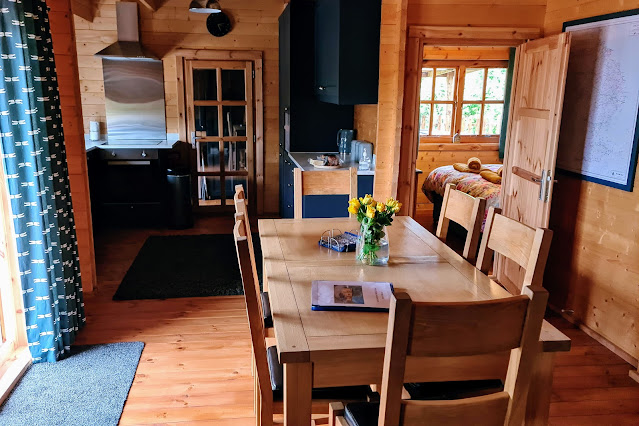 View of the inside of tythe lodge holiday let. Solid wood dinding table that seats six. Blue Kitchen blue dragonfly patterned curtains covering double patio doors. View through wooden door into en suite bedroom.