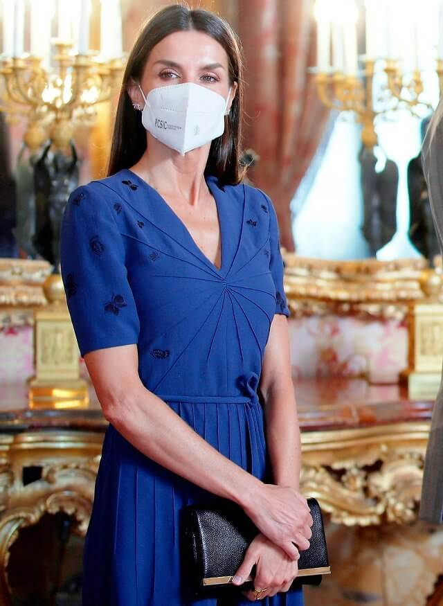 Queen Letizia wore a blue v-neck embroidered crepe dress from Bottega Veneta. Carolina Herrera clutch