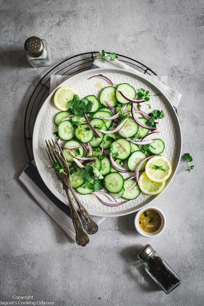 This vegan cucumber salad served on a plate with fork. The plate placed on a white kitchen towel.