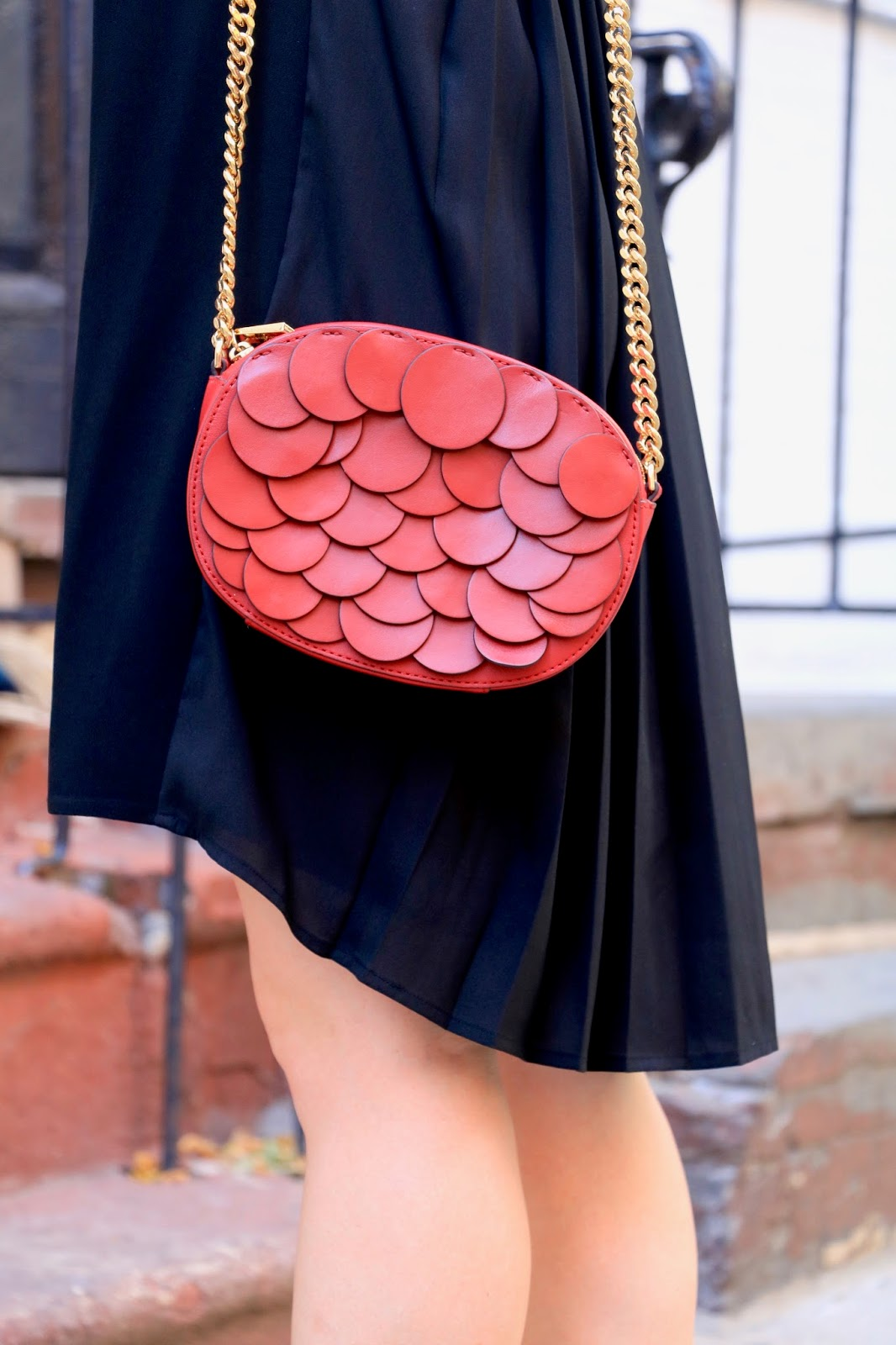 Fashion blogger Kathleen Harper carrying a red petal purse by Michael Kors
