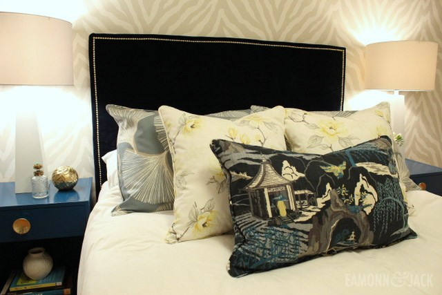 pillows piled on a bed with a blue headboard