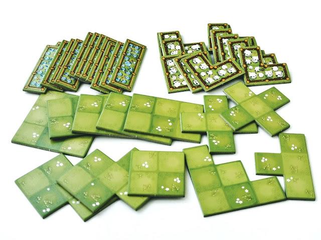 na zdjęciu rozłożone w rzędach na stole kafle, elementy gry