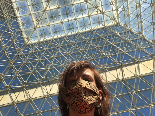 woman inside tall glass pyramid structure