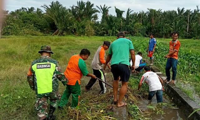 Babinsa Hermanto bersama Warga Gotong Royong Membersihkan Draenase