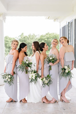 bride with bridesmaids in lavender dresses and greenery bouquets