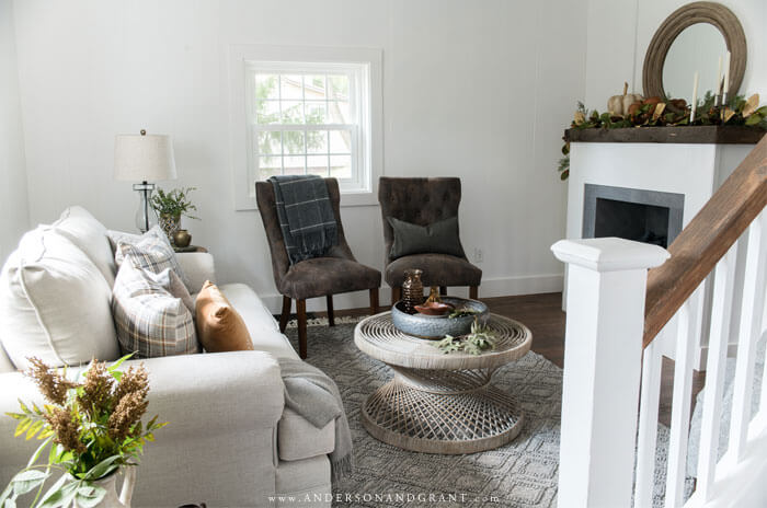 A modern farmhouse style living room decorated for fall with neutrals and gold.