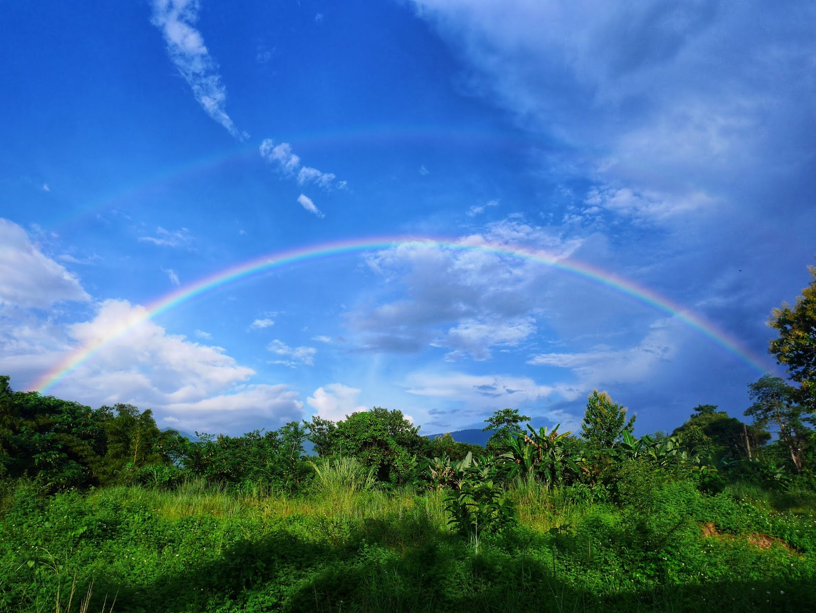 a double rainbow over the jungle in Vang Vieng, Laos