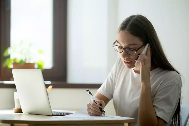 Mulher no telefone escrevendo no papel com caneta