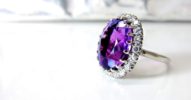Photo of an amethyst ring against a white backdrop.
